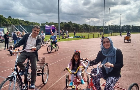 A family of 3 cycling at the Festival in the Park 2017 in Wythenshawe Park Athletics Track