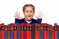 """a smiling girl with a load of books spelling """"NEVER STOP LEARNING"""" 