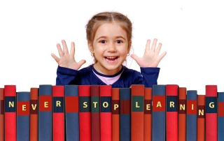 "a smiling girl with a load of books spelling ""NEVER STOP LEARNING"" 