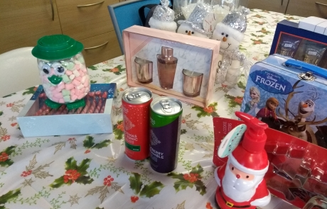 Prizes for Lifted's Christmas Bingo 2019 - includes festive M&S gin, Christmas-themed wine glasses, booming peony diffuser & candle set, Frozen Trumps pack with tin box, Gray's original Esquire shower gel set