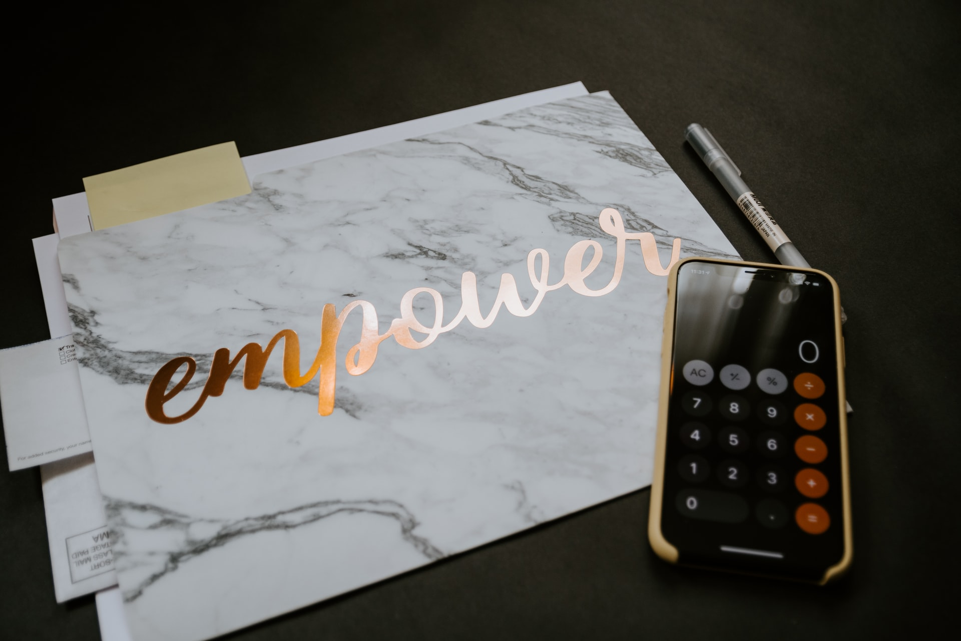 a calculator and a folder containing some documents; the folder has 'empower' printed on it | photo credit: Kelly Sikkema on Unsplash.com