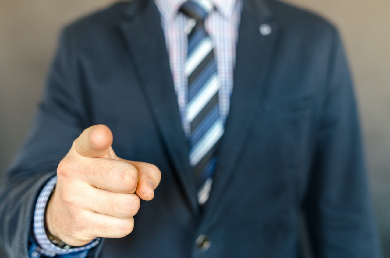 a person wearing a suit pointing towards the viewer